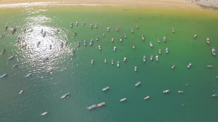 Sailboats and fishing ships in blue sea near sandy shore aerial landscape. Fishing boats and sailing ships in sea parking drone view.