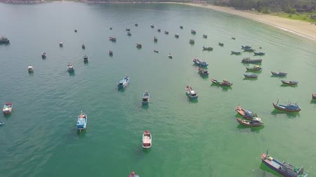 Fishing boats and sail ships in blue sea water at parking aerial landscape. Drone view sea boats and sailing ships in parking. Stock mozgókép