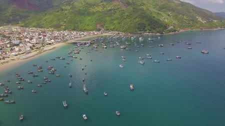 Ships and fishing boat standing in sea bay and blue water and green mountains aerial landscape. Drone view sailing ships in sea harbour.