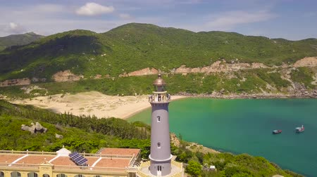 Lighthouse on green mountains and ships sailing in blue sea aerial view. Landscape from above flying drone lighthouse on tall mountain cliff and boat sailing in turquoise sea. Wideo