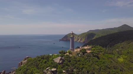 Drone view light house on green mountains and blue sea on clear horizon. Aerial view sea lighthouse on mountain cliff and blue sky landscape.