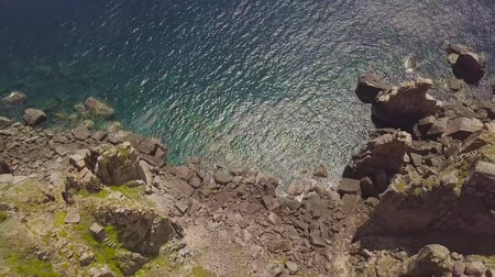 Rocky cliff on shore and blue sea drone view. Top view cliff mountain and turquoise ocean water. Landscape from flying drone rocky sea shore.