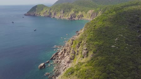 Green mountain with rocky cliff and ships sailing in blue sea aerial view. Beautiful landscape from drone mountain cliff and blue sea on skyline.