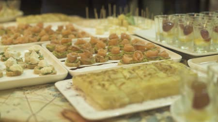 Snacks and canape on buffet table at event. Appetizing snacks on party table at holiday evening. Wideo