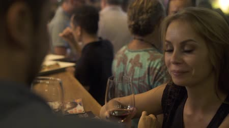 şarap kadehi : Woman and man clinking glasses with red wine and drinking at event party. Woman drinking red wine from wineglass in restaurant.