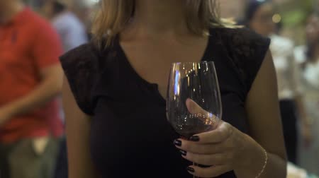 wine red : Woman in black dress holding in hand red wine glass close up. Young woman with wineglass in hands in restaurant.
