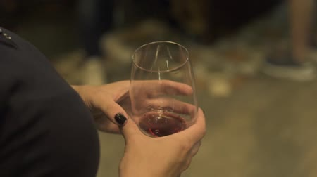 şarap kadehi : Female hands holding red wine glass in restaurant. Close up woman with red wineglass and black clothes walking inside restaurant.