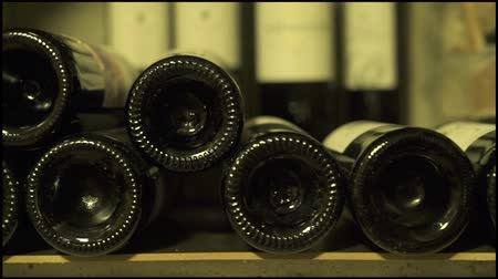 fermenting : Wine bottles lying in stack at cellar close up. Glass bottles of red and white wine stored in stone cellar.