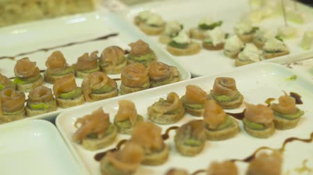Delicious snacks and canape on table at event party. Close up appetizing snacks on party table at holiday evening.