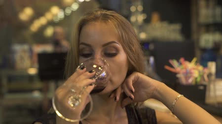 Face woman drinking red wine from wineglass while degustation in restaurant. Woman drinking red wine from glass at event party.