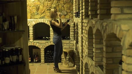 vinné sklepy : Woman drinking red wine from glass and holding bottle in hand in cellar. Woman winemaker tasting red wine from glass in traditional cellar. Dostupné videozáznamy