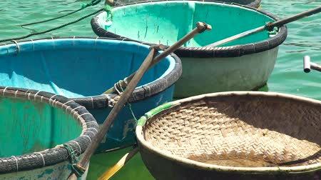 vime : Round boats with paddles for floating and fishing in sea water close up. Traditional vietnamese boats for fishing and floating in blue sea. Vídeos