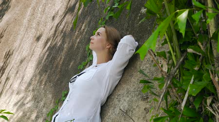 hajló : Happy woman resting lean back on mountain at summer day. Relaxing girl leaning back on big stone and enjoying summer day.