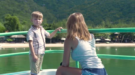 vztahy : Little son talking with mother aboard sailing ship in summer cruise on sea. Young mom together son traveling on ship sailing in ocean while summer vacation. Dostupné videozáznamy