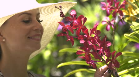 orchidea : Young woman in hat enjoying blooming flowers in summer garden. Girl sniffing scent of blooming orchids in flower garden at sunny day.