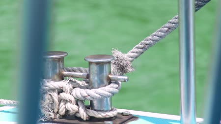 hawser : Rope on ship board deck sailing in blue sea water background. Close up rope on aboard sailing boat in ocean. Navigation, shipping, sea transport and equipment.
