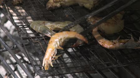 carvão gigante : Close up shrimps on barbeque grill while picnic. Shrimps barbeque meat on grill on fire and coal. Outdoor picnic, sea food cooking concept.