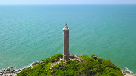 námořní : Light house on green island in turquoise sea aerial landscape. Drone view tall lighthouse on rocky island in blue ocean landscape.