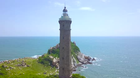 világítótorony : Sea light house on rocky shore in sea on blue skyline landscape. Drone view lighthouse on green island in blue ocean. Stock mozgókép
