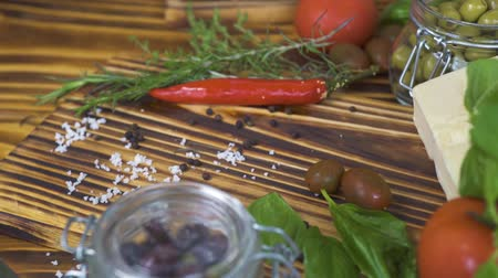 ocet : Fresh vegetables pepper, tomato, onion, garlic and herbs rosemary, salt, olives for cooking tracking shot. Close up vegetables and seasoning for cooking food. Wideo