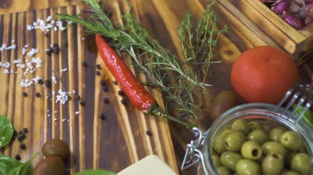ocet : Close up vegetables pepper, tomato, onion, garlic and herbs rosemary, salt, olives for cooking food on kitchen. Trecking shot vegetables and seasoning herbs on wooden table. Wideo