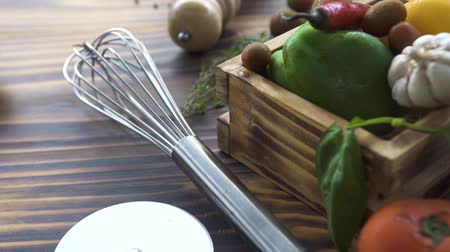 酢 : Kitchen corolla, pizza knife, herbs, vegetables pepper, tomato, onion, garlic, salt, olives for cooking food on table. Close up vegetables and seasoning for food preparation on wooden table.