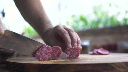 chefs table : Close up knife in male hands cutting sausage salami on wooden table. Chef cook cuts into thin slices fatty sausage pepperoni for cooking pizza. Process preparation ingredients for italian pizza. Stock Footage
