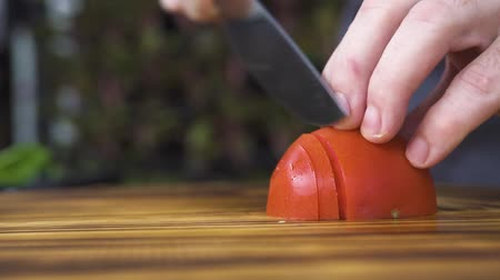 kesme tahtası : Knife slicing fresh tomato on board close up. Hands of chef cook cutting tomato for pizza. Fresh ingredient for vegetarian cuisine. Mediterranean diet and healthy nutrition. Cooking vegetable salad.