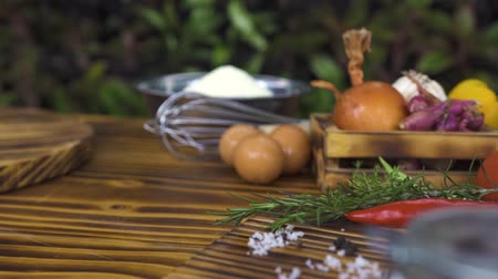 apetitoso : Food composition from colorful vegetables, seasoning, flour and eggs on wooden table. Vegetale background tracking shot. Ingredient for cooking food on kitchen table. Healthy nutrition and dieting.