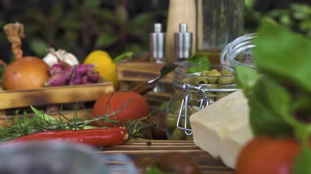 ocet : Tracking shot food composition close up. Food background from vegetable, olives, herbs, cheese, seasoning on wooden table. Fresh ingredients for cooking on kitchen table. Healthy diet and nutrition.