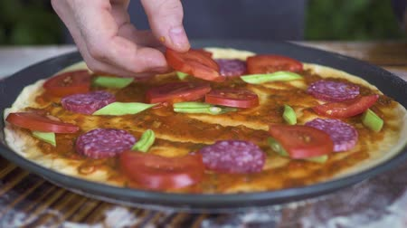 baharatlı alman sosisi : Raw italian pizza with tomatoes, pepperoni sausage and green beans on table. Pizzaillo hands making pizza in italian pizzeria. Process preparation national cuisine. Cooking traditional food.