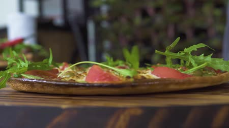 calabresa : Fresh herbs falling on hot italian pizza slow motion. Close up pizza with fresh herbs in pizzeria. Food seasoning concept. Cooking traditional food. National italian cuisine.