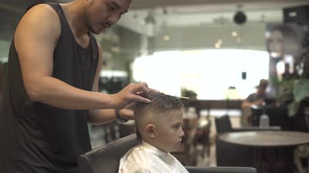 shaver : Hairstylist cutting little boy with hair machine in barbershop. Close up boy haircut in hairdressing salon. Boy haircut with comb and electric shaver. Hairdresser doing children hairstyle.