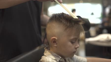 kurutma : Boy hairstyle with dryer in barbershop. Children hair drying in barber salon. Hairdresser styling hair little boy with dryer. Finish hairdressing in barbershop. Children hairdo concept.