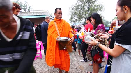 dát : KANCHANABURI, THAILAND -  MAR 25, 2015: Unknown People, give food offerings to a Buddhist monk in Morning, Sangkhlaburi, Kanchanaburi Thailand. As the successor to a long tradition.