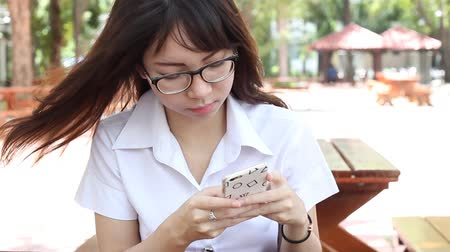 uniforme : Portrait of thai woman student university beautiful girl using her smart phone.
