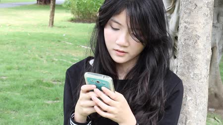 délkelet Ázsia : Portrait of thai student teen beautiful girl using her smart phone and smile. Stock mozgókép
