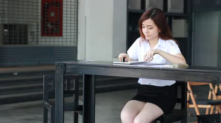 ül : Portrait of thai student university beautiful girl typing tablet.