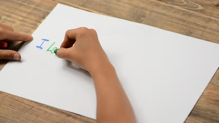 truly : Boy hand writing on white drawing paper by crayon. I love dad. Stock Footage