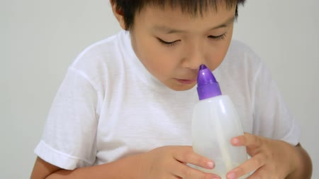 aspirator : Asian boy wash nasal by inject saline water from plastic bottle for a smooth aspiration
