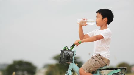 veículo aquático : Asian boy in white shirt sit on bicycle drink fresh water from plastic bottle Stock Footage
