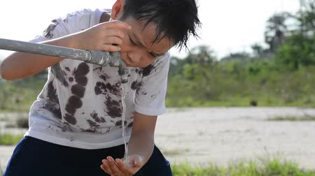 mycie rąk : Asian boy in dirty shirt using water from the old faucet in the dry land Wideo