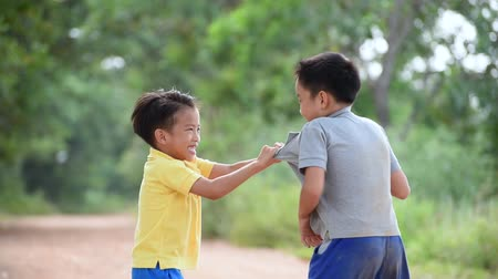 médio : Two boy angry and fighting by punch on the other on the urban road during summer time. Stock Footage