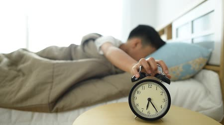 uyanmak : Young boy wake up after the antique black alarm clock ring in the morning.