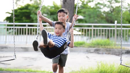asian family : Two young asian boy play a iron chain swinging at the playground under the sunlight in summer.