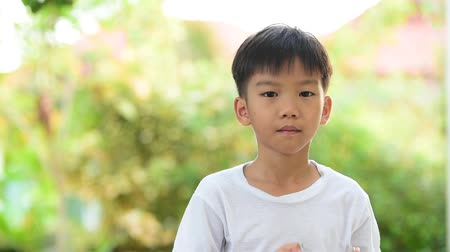leite : Young Thai boy in white shirt drinking milk from glass in the garden