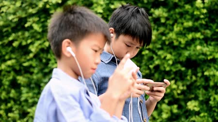 mal : Selective focus of preteen Asian Thai boy got pain at his eye during using smartphone to play game in his home garden. Technology and health concept Vídeos