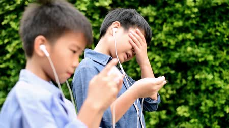 improve : Slow motion of preteen Asian Thai boy is using smartphone to play game in his home garden. Technology and health concept