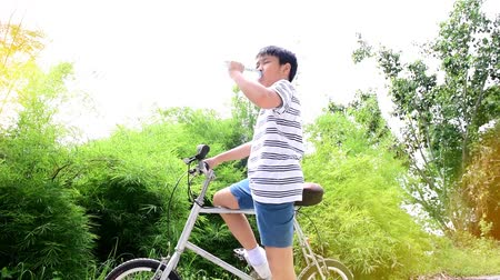 consumir : Slow motion of Preteen Asian Thai boy drinking water from plastic bottle during cycling on a bike in a garden.