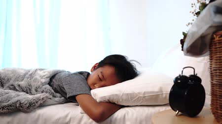 dobranoc : Young Asian boy sleeping on a white bed and awake to turn off alarm clock. Wideo